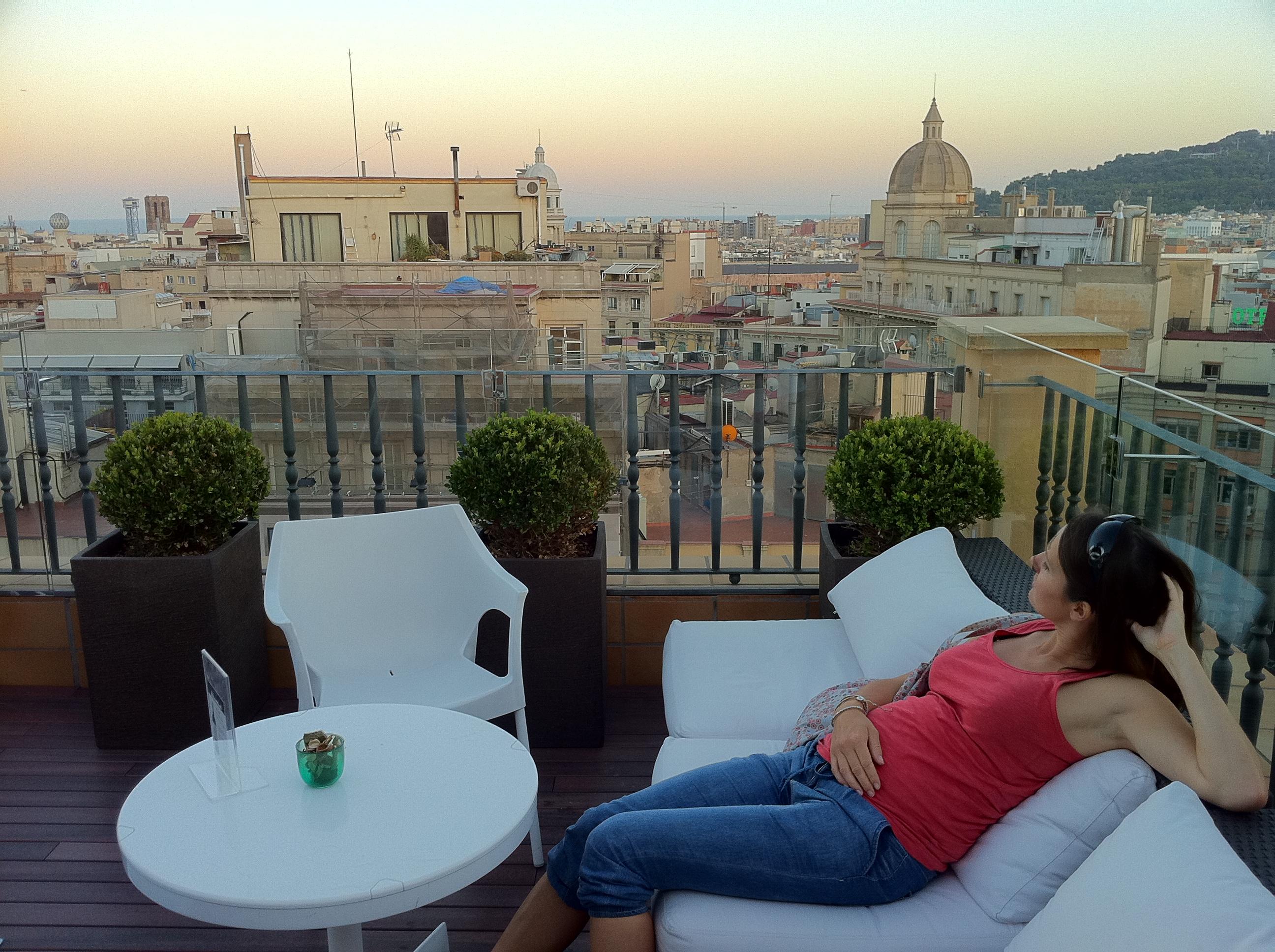 """alt=""""Städtetrip Barcelona, Frau auf einer Dachterrasse mit Ausblick auf die Stadt"""""""