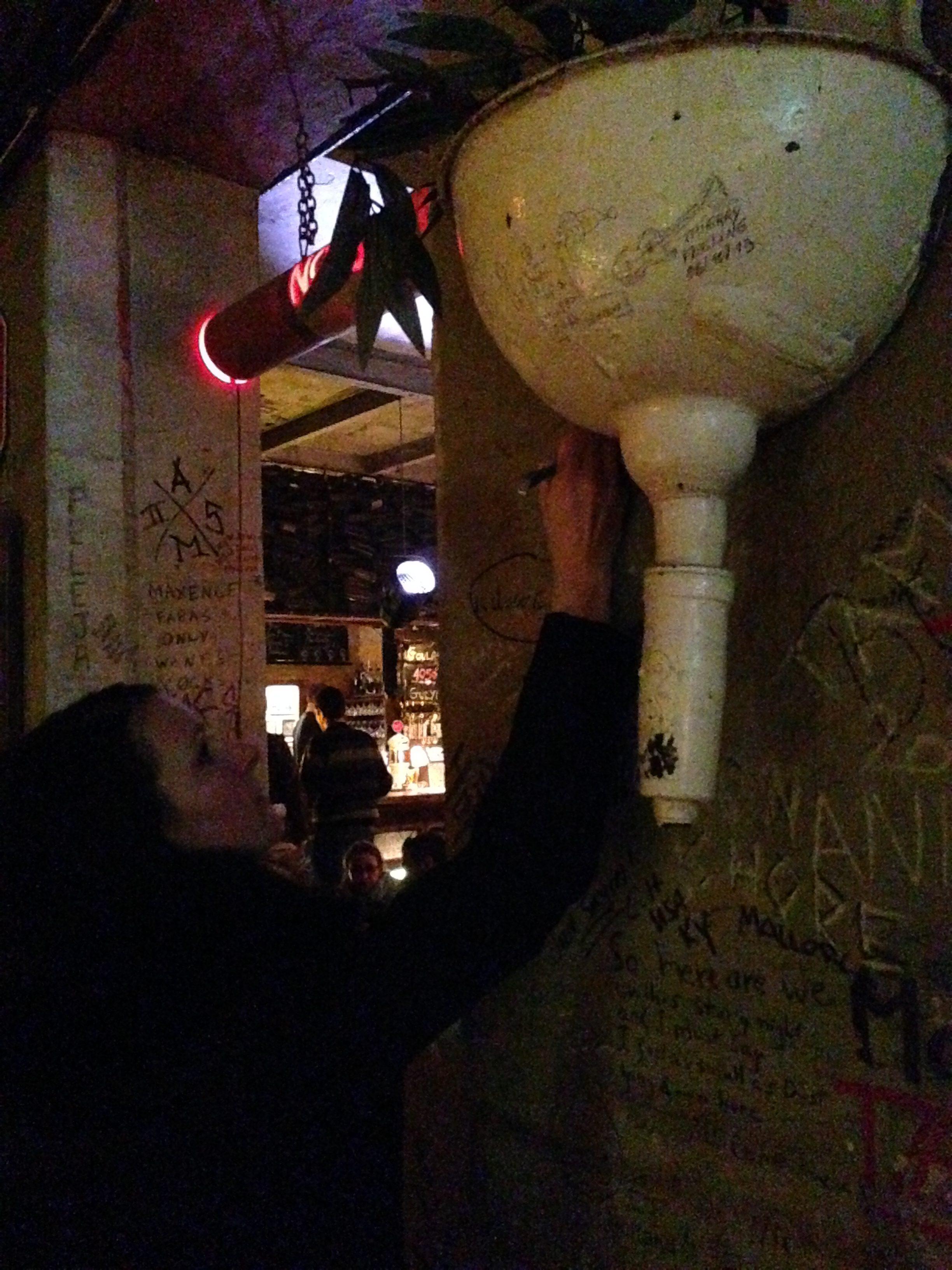 """alt=""""Junge Frau schreibt mit Edding an eine Wand in der Szimpla kert Bar in Budapest im Jüdischen Viertel"""""""