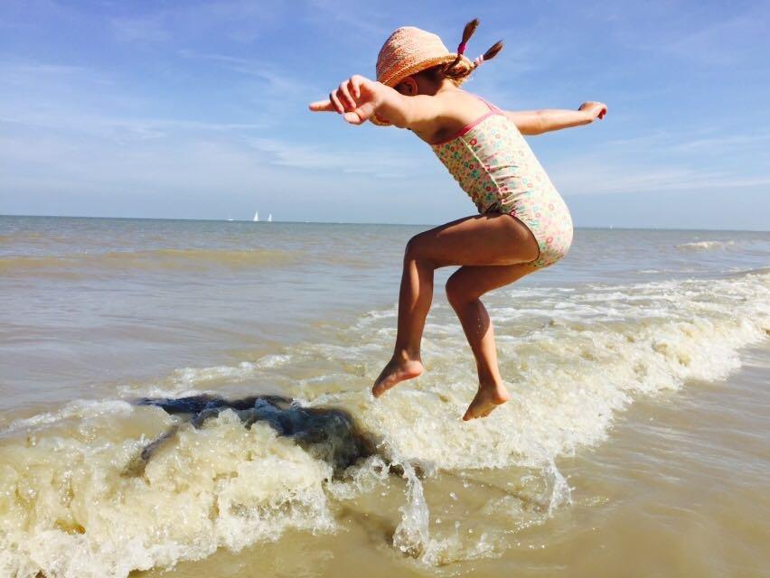 Springendes Mädchen am Strand in Cadzand