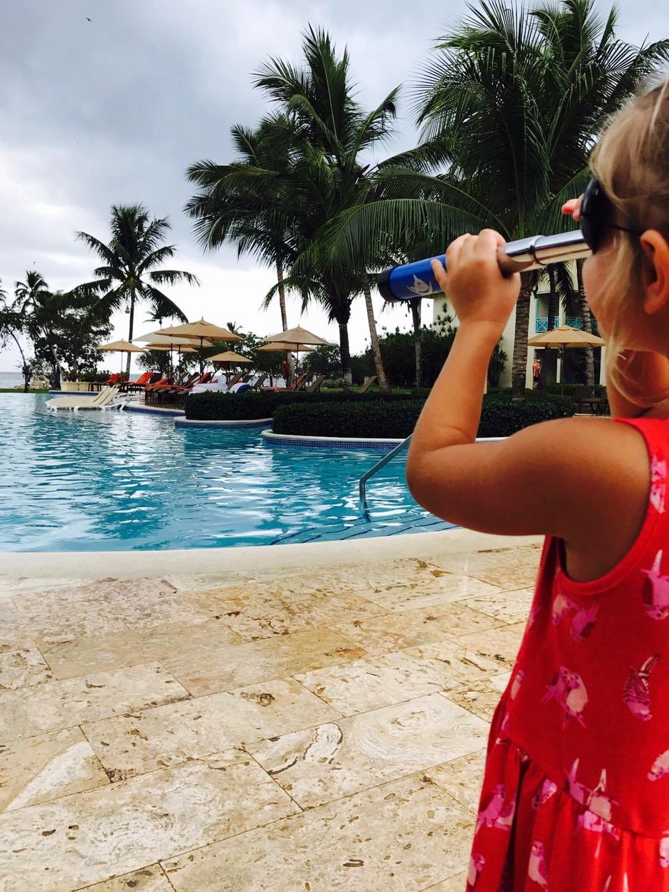 Mädchen von hinten schaut mit einem Fernrohr auf den Pool vom Dreams La Romana am Bayahibe Strand, Dominikanische Republik
