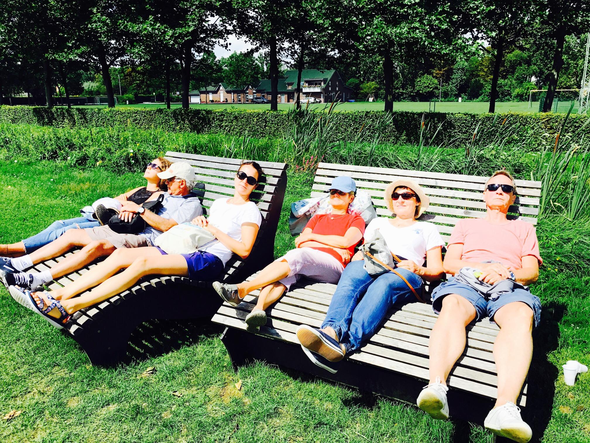Familien beim Ausruhen auf Holzliegen im Gartenschaupark Rietberg