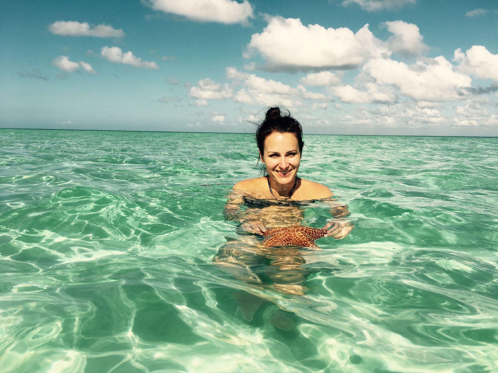 Frau im Meer auf einer Sandbank mit Seestern in der Hand, Saona Island