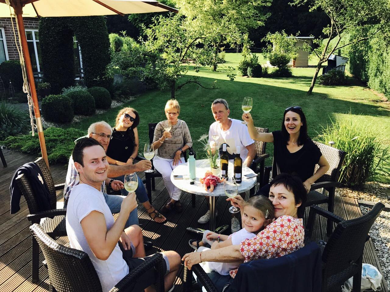 Familie in einem Garten am Tisch sitzend, Hotel Waldblick Deppe in Bad Waldliesborn