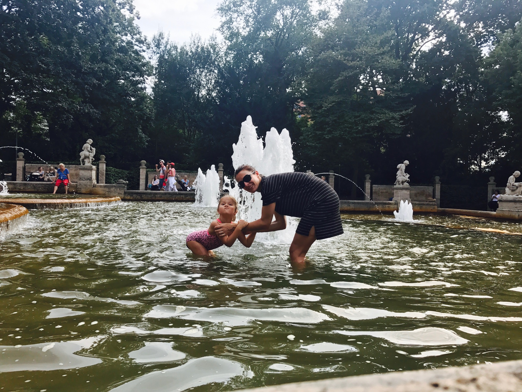 Mutter und Tochter nehmen kleine Abkühlung im Märchenbrunnen im Volkspark Friedrichshain, Berlin