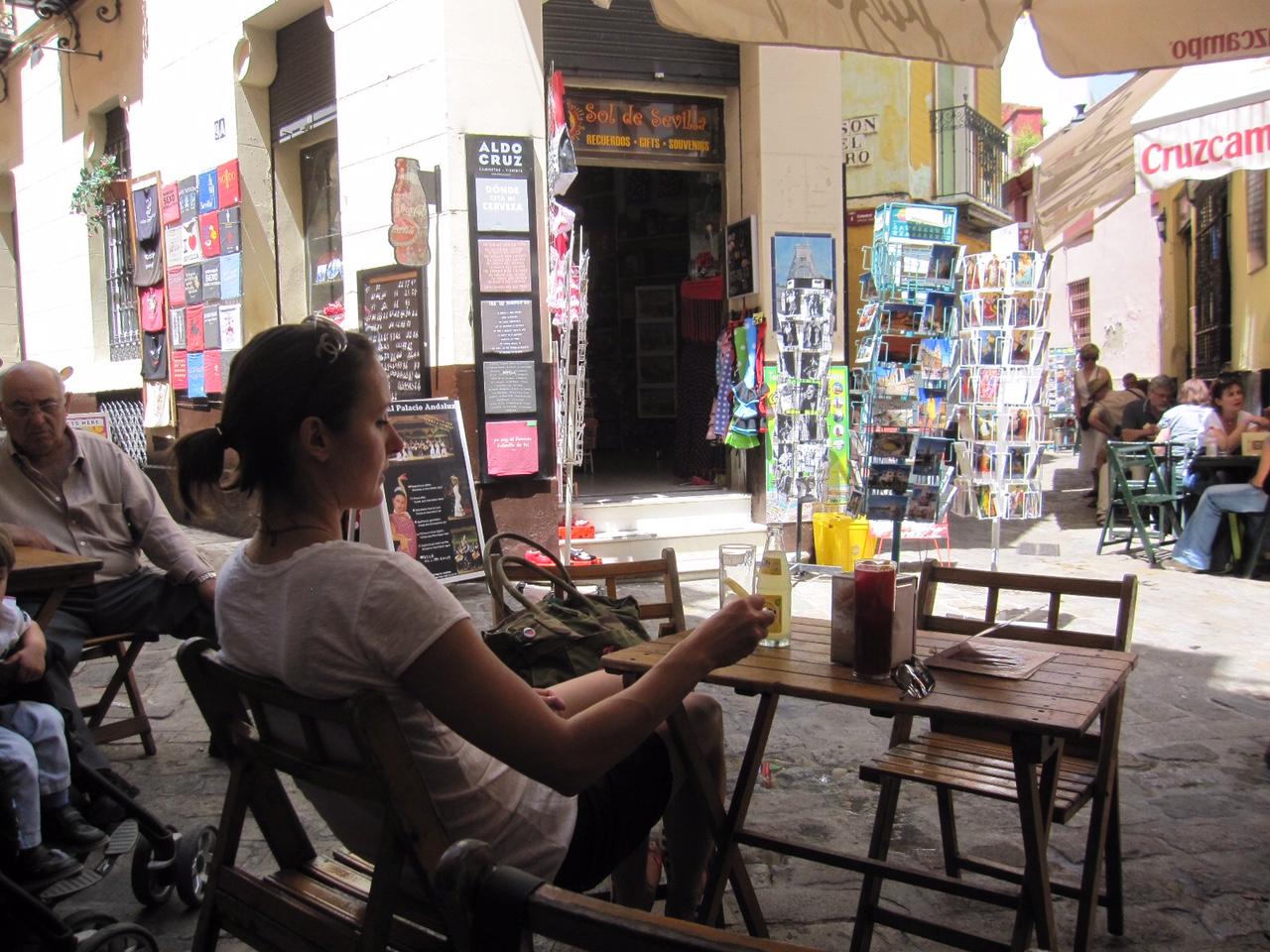 Frau sitzt in Bar in der Altstadt von Sevilla, Andalusien