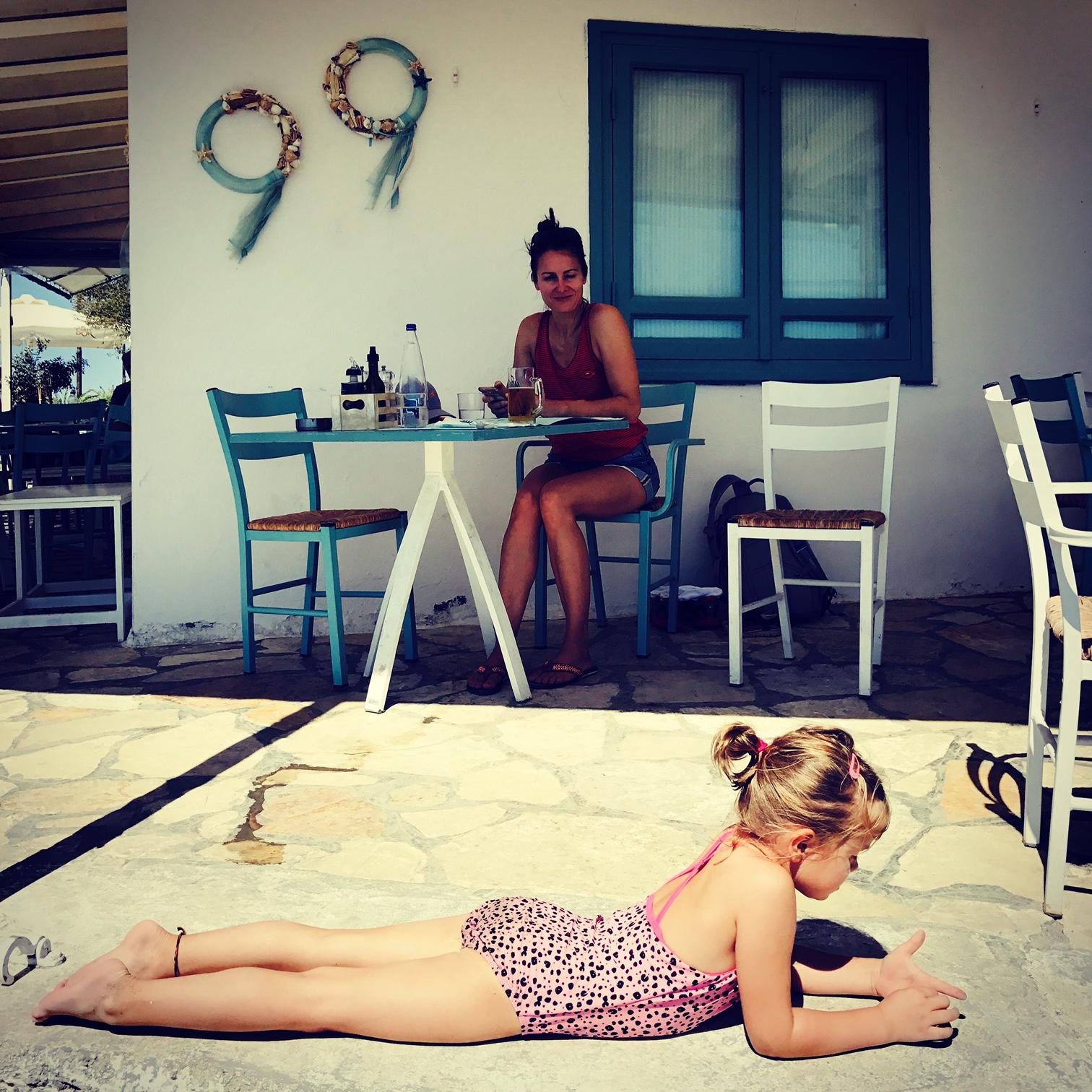 Mutter im Hintergrund auf einem Stuhl, kleines Mädchen im Vordergrund liegend vor der Bar Flisvos Seaside, Korfu