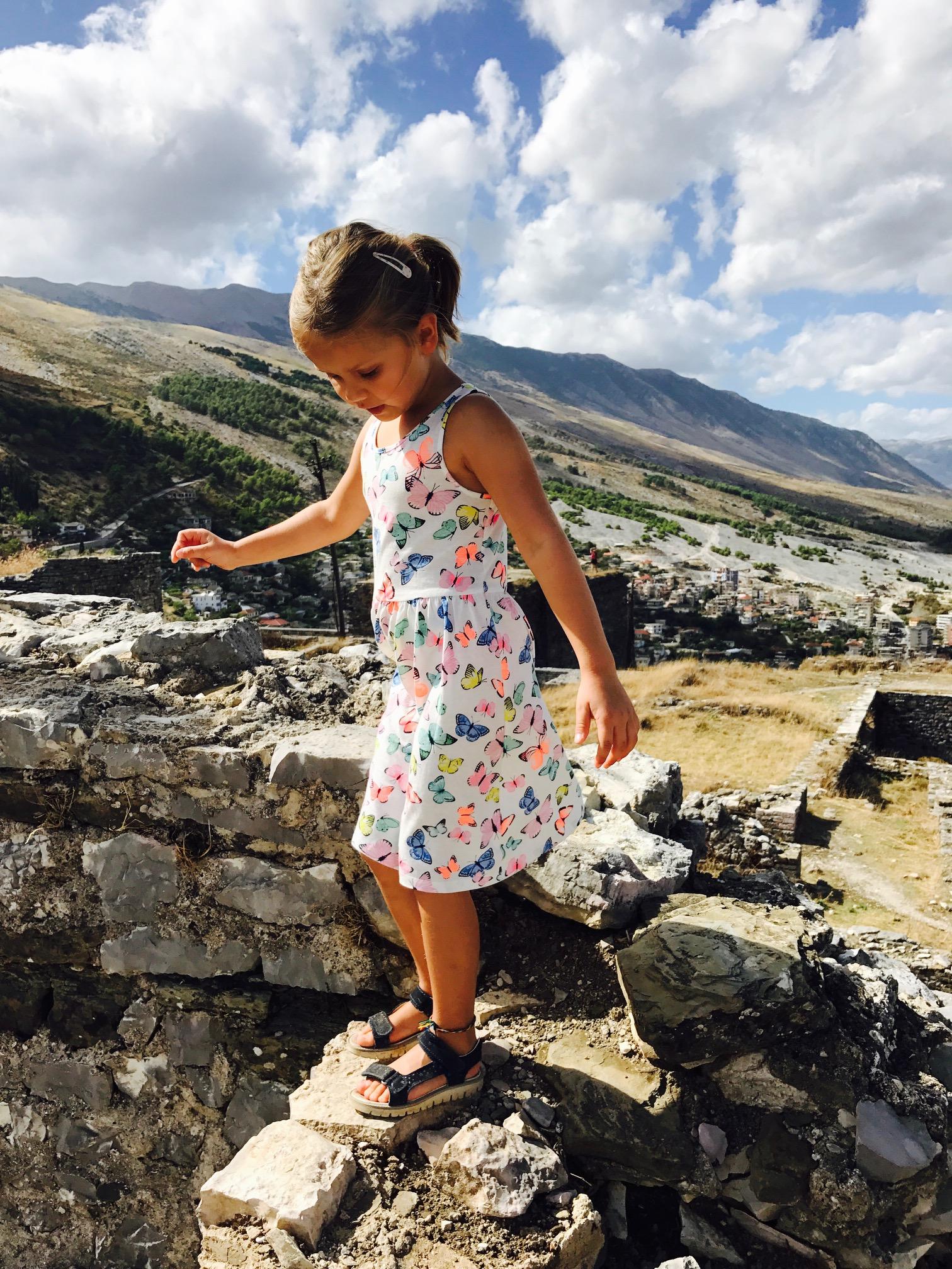 Kleines Mädchen balanciert auf einer Mauer bei der Gjirokastra Burg, Albanien