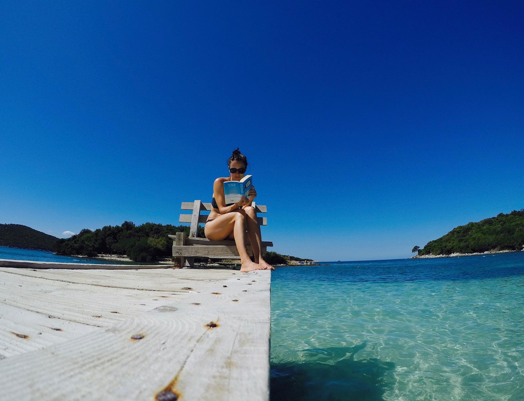 Frau auf einem Holzsteg, lesend, am Ksamil Beach, Albanien