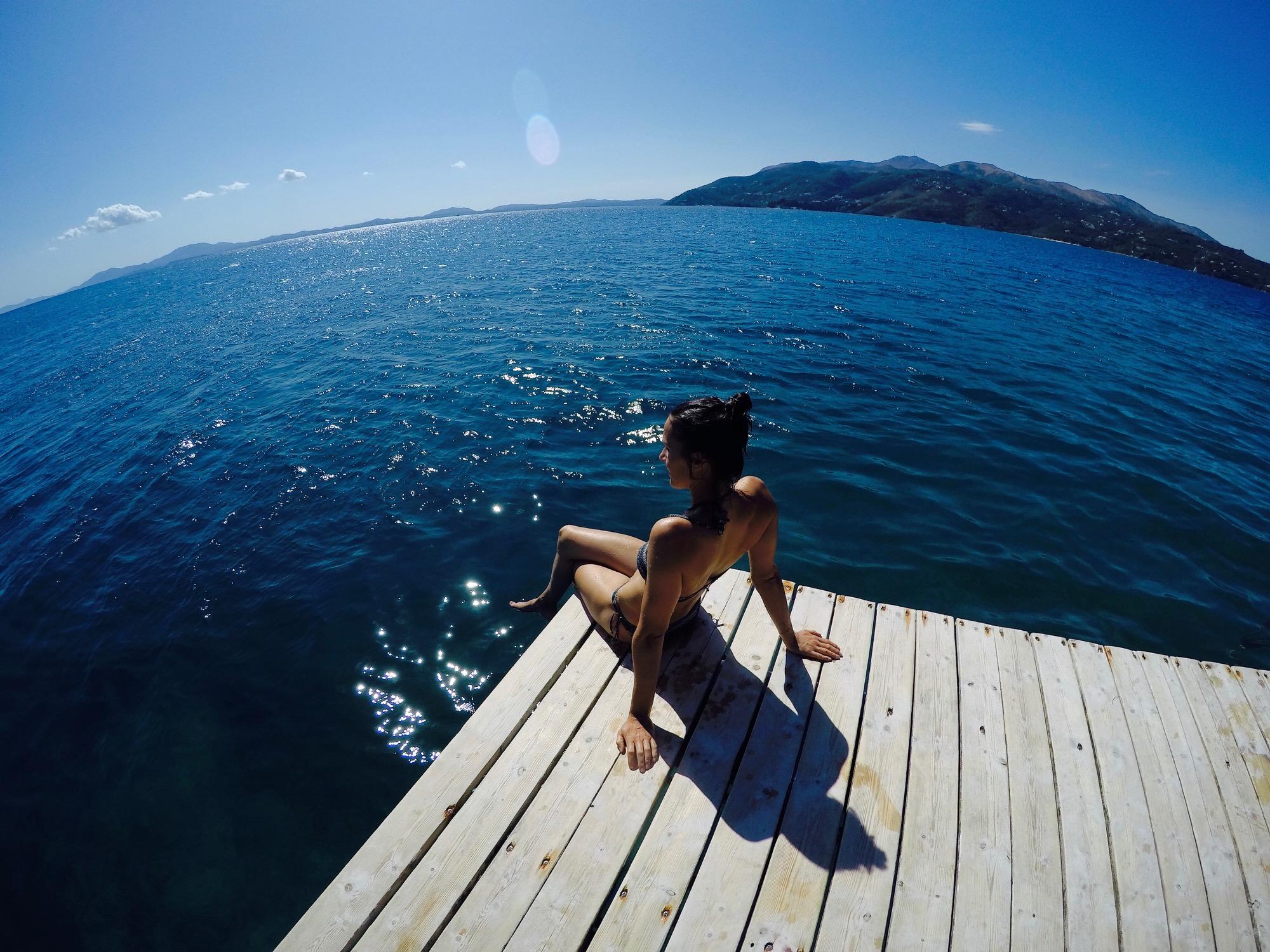 Frau sitzt auf einer Plattform im Meer bei der Pema e Thate Bucht, Albanien