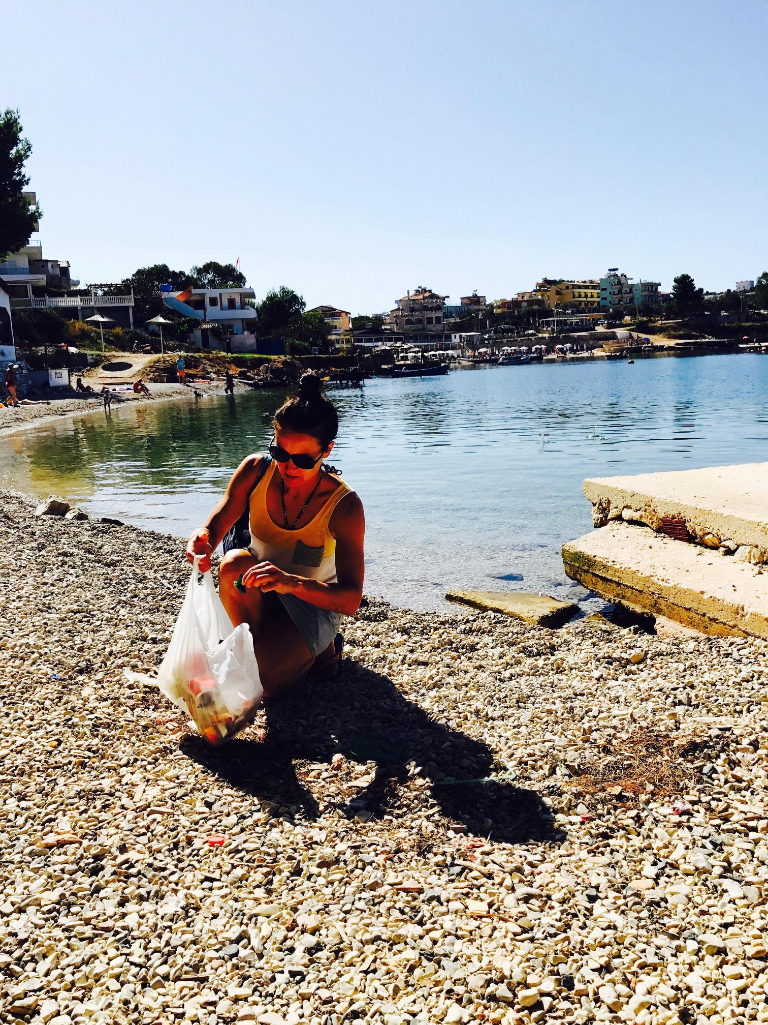 Frau sammelt Müll am Strand auf, Ksamil