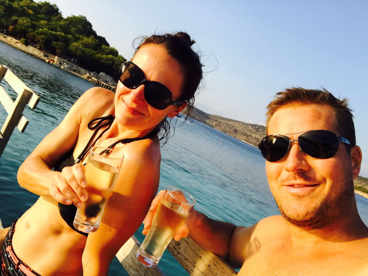 Frau und Mann stoßen an und sitzen dabei auf einem Holzsteg, die Sonne geht unter, sie lächeln in die Kamera, Ksamil, Albanien