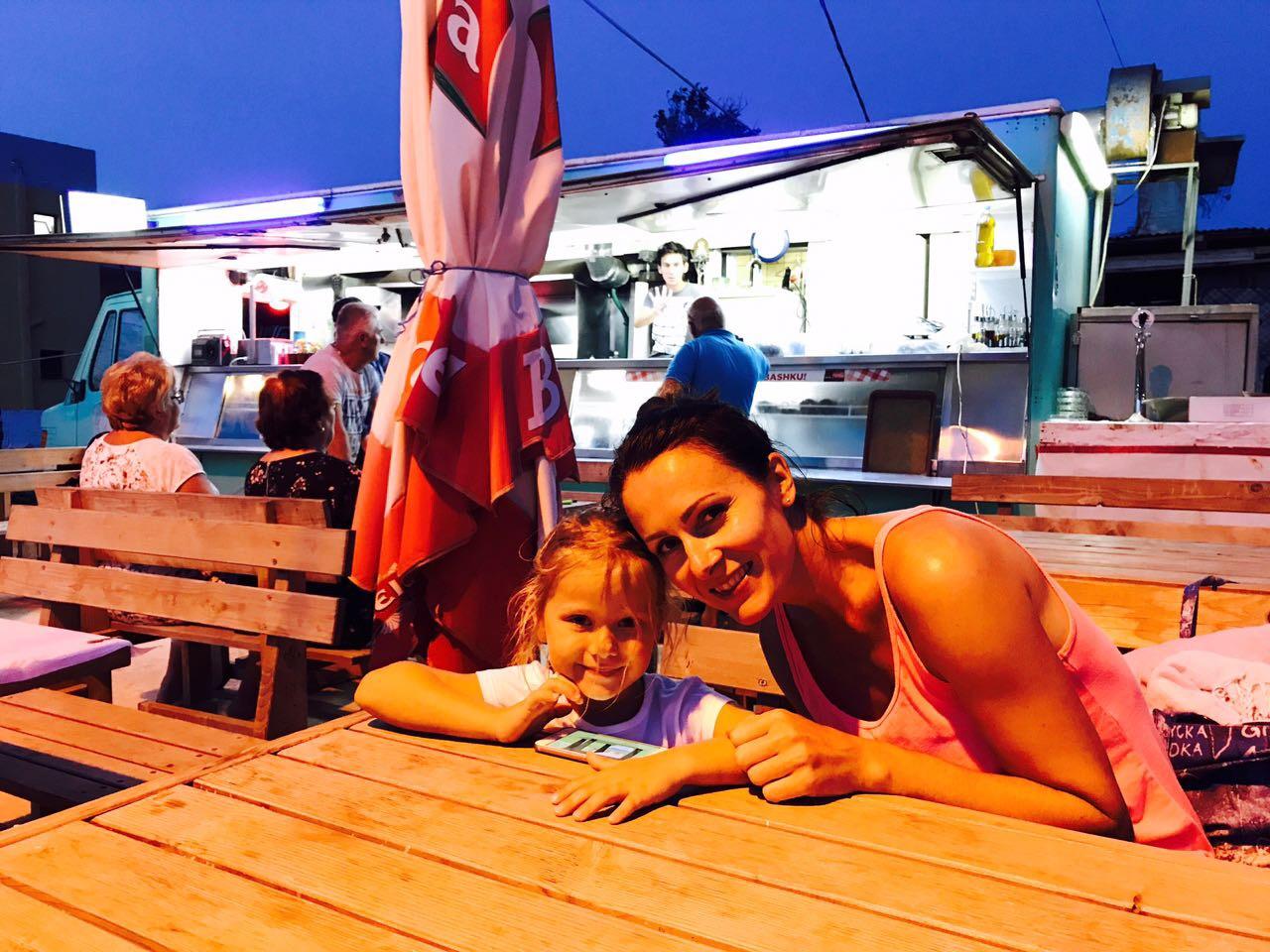 Mutter und Tochter am Tisch sitzend in einem Straßengrill in Ksamil, Albanien