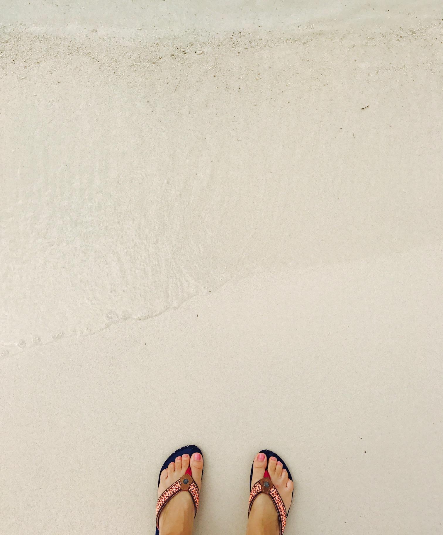 Zwei Füße auf weißem Sand am Ksamil Beach, Albanien
