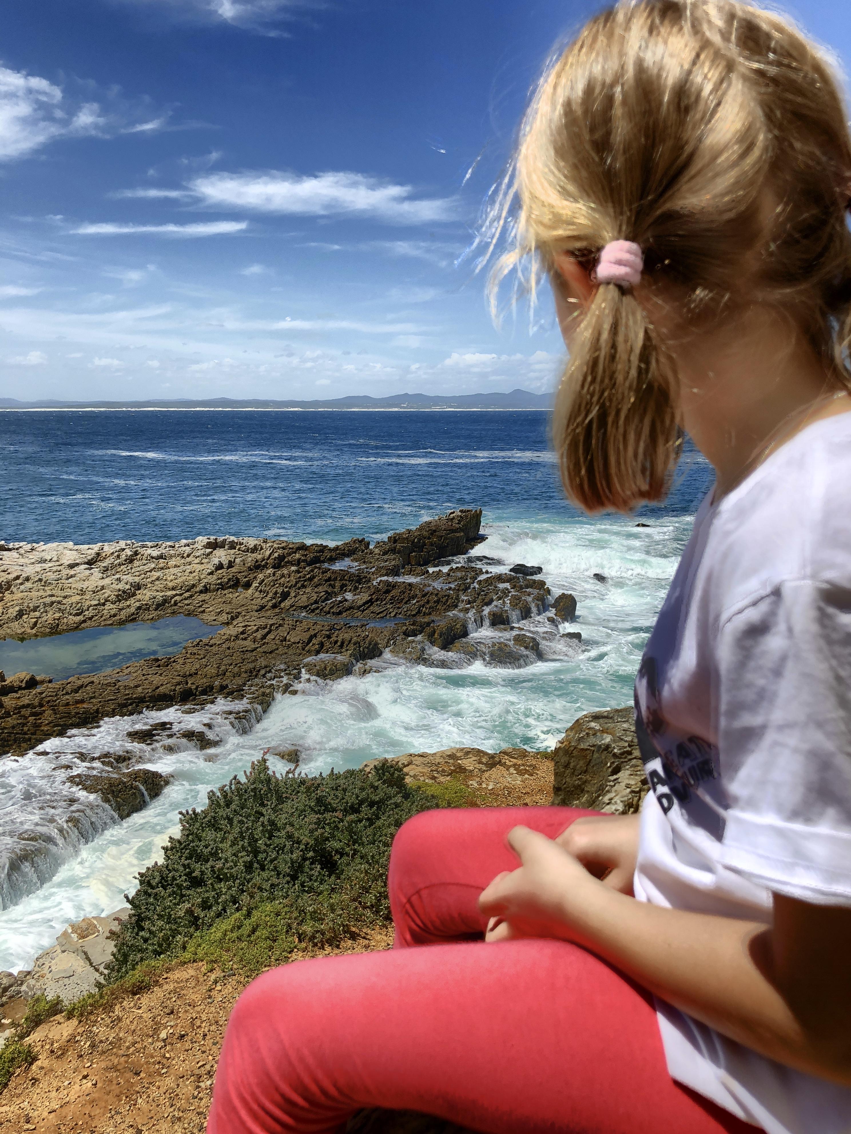Kind schaut aufs Meer hinaus, Hermanus, Südafrika