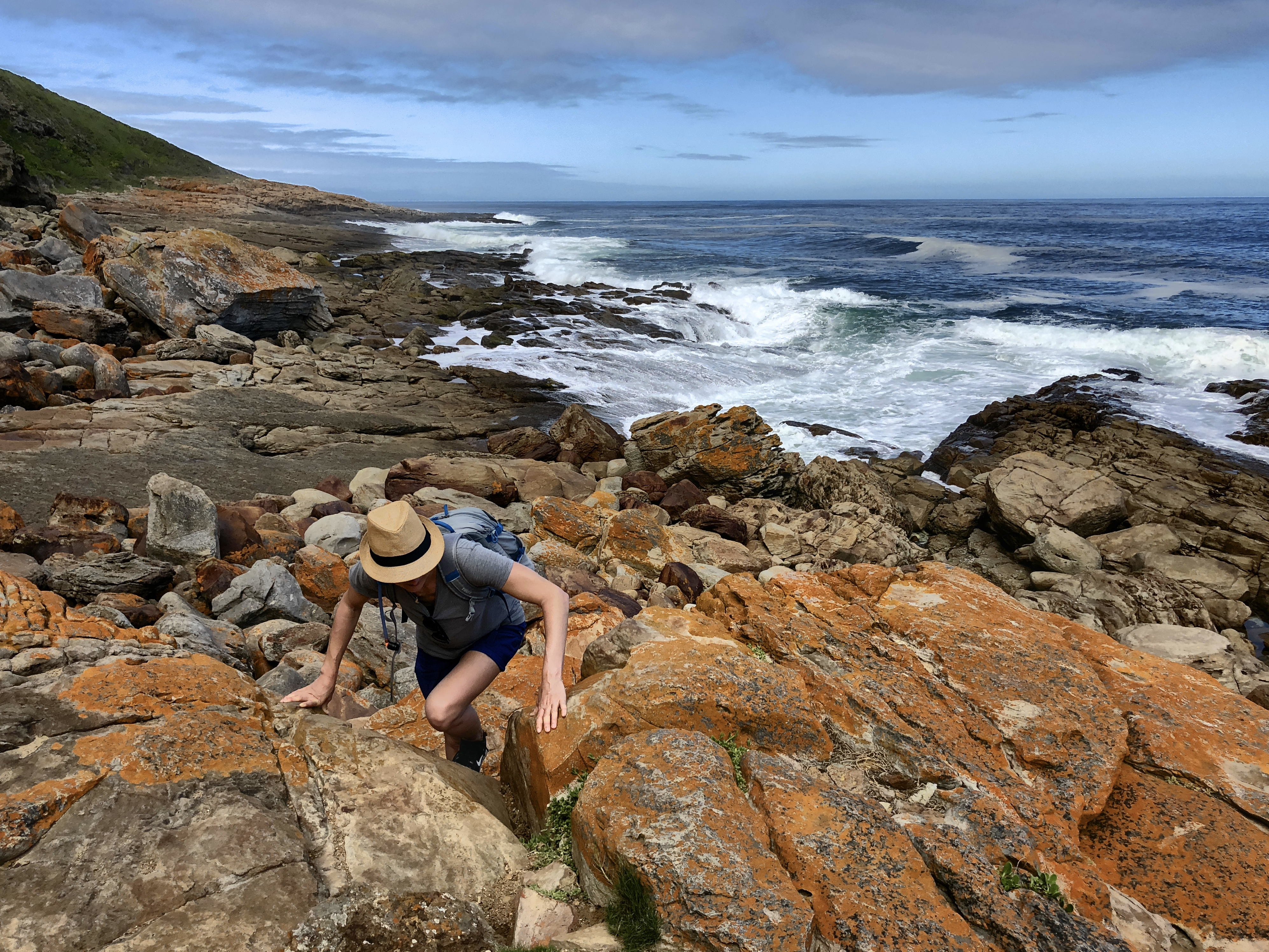 Frau beim Klettern auf Robberg Island, Südafrika