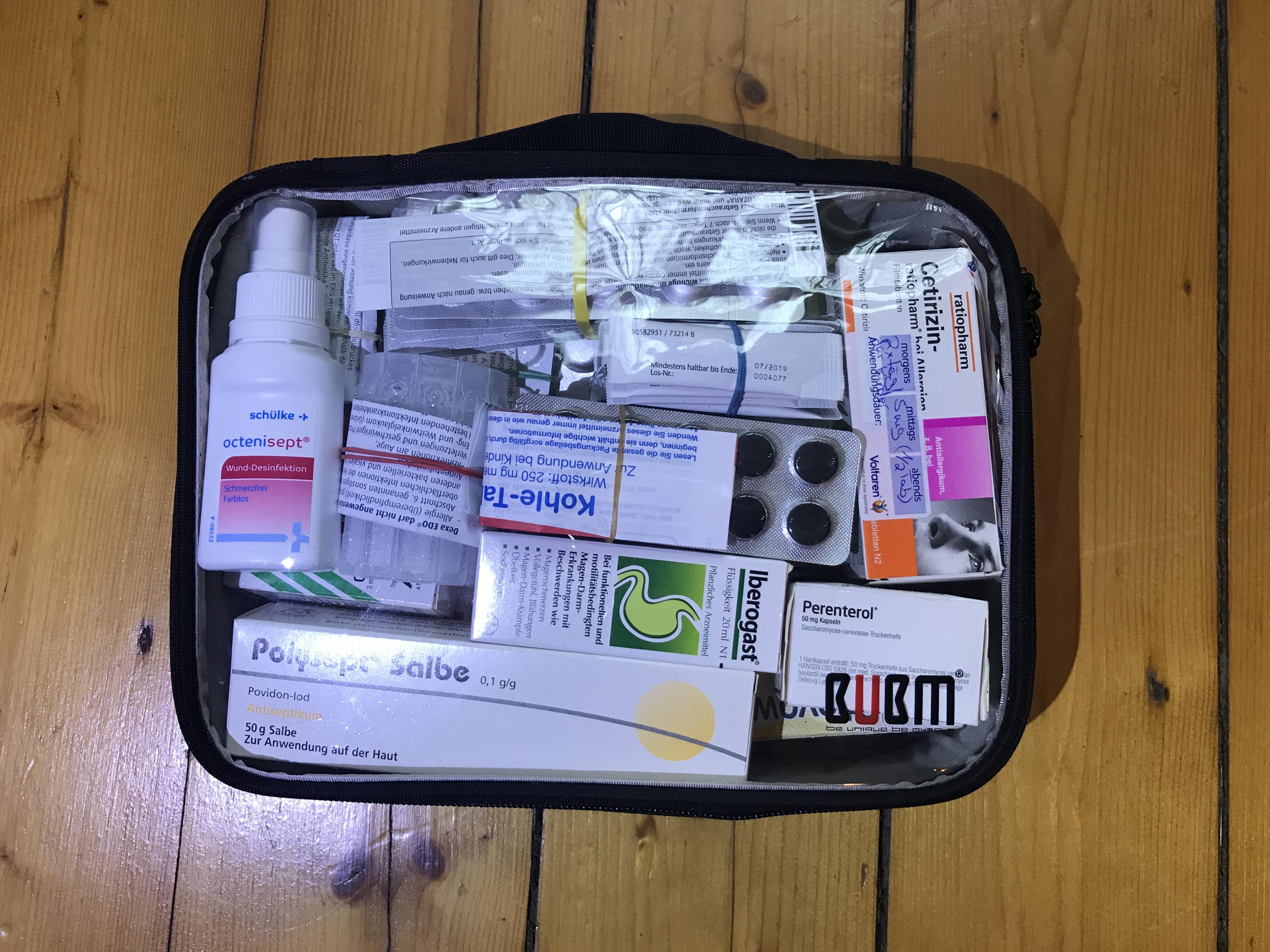 Das Bild zeigt die Reiseapotheke zusammengepackt in einer durchsichtigen Box
