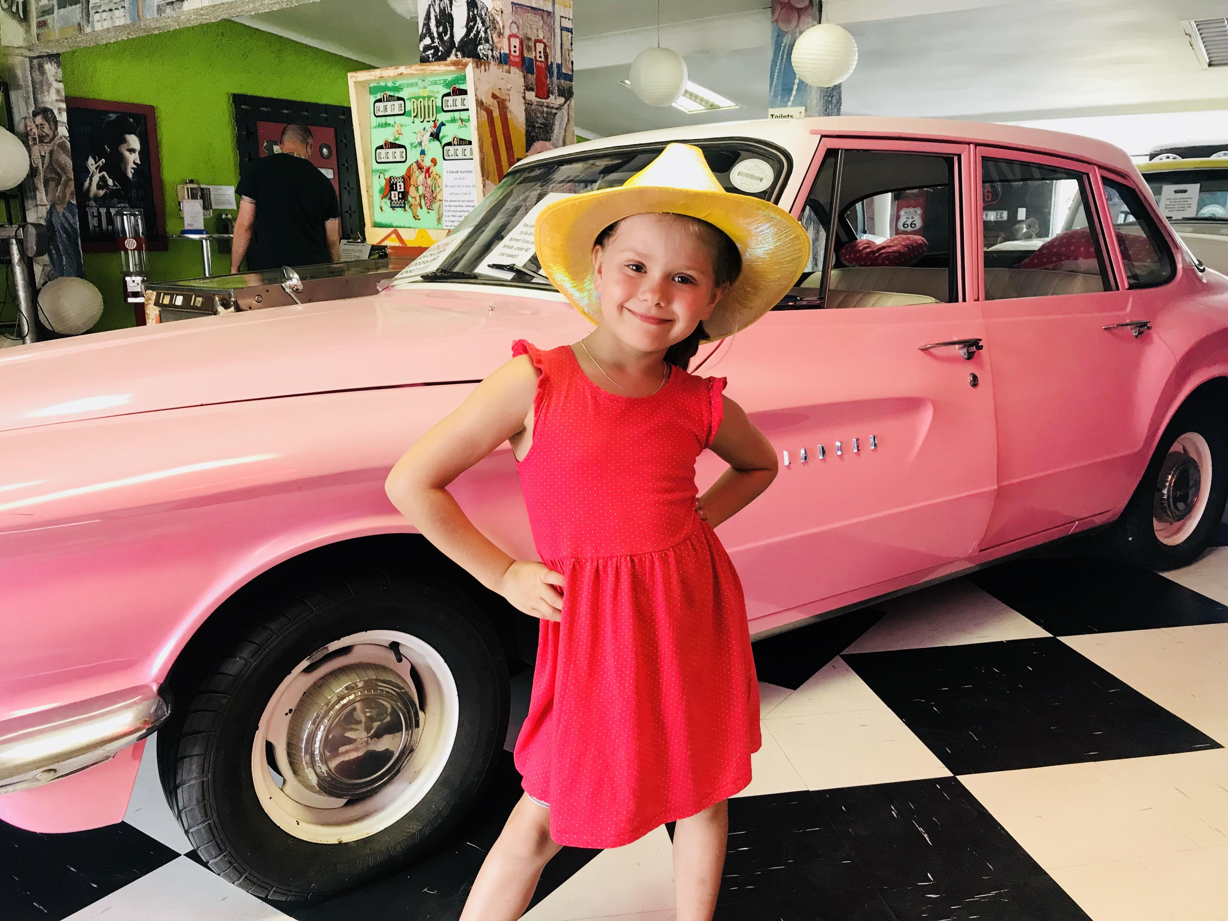 Kleines Mädchen post vor einem pinken Cadillac im Diner im Storm River Village, Südafrika