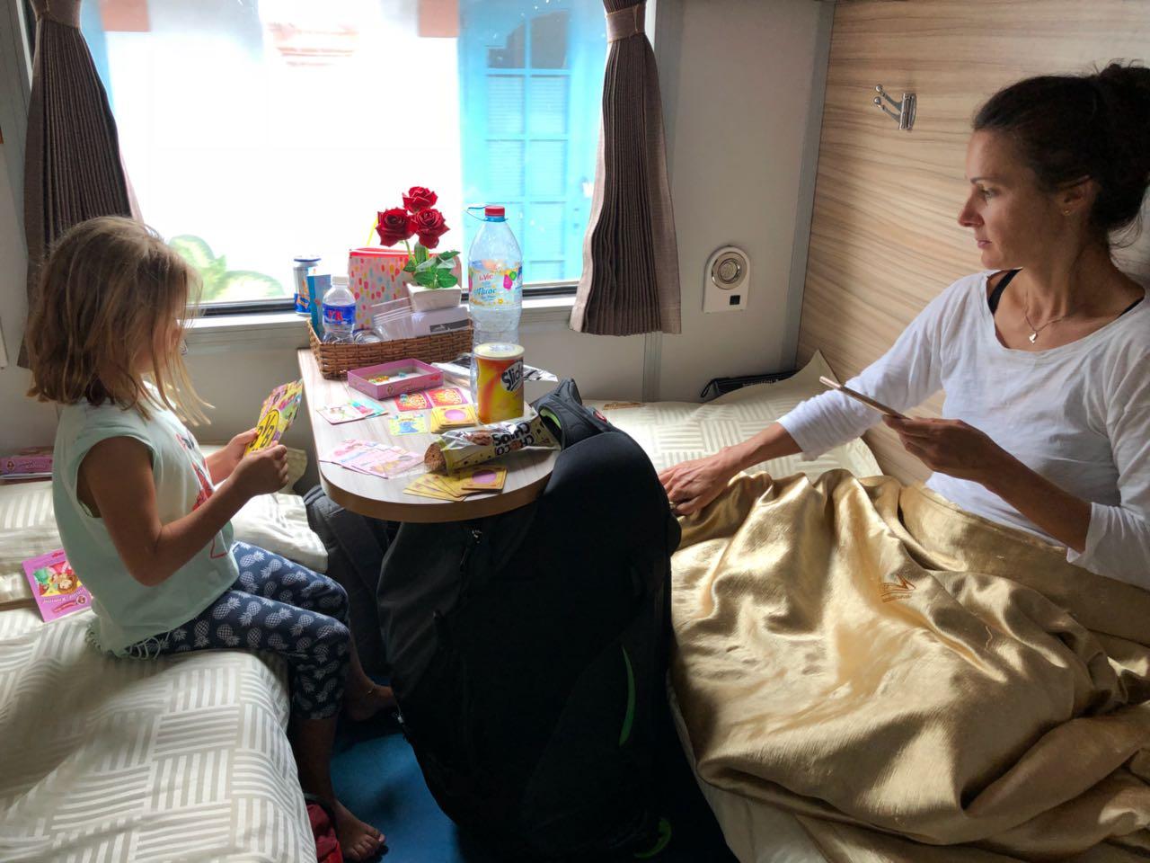 Mutter und Kind spielen Karten in einem Zug in Vietnam