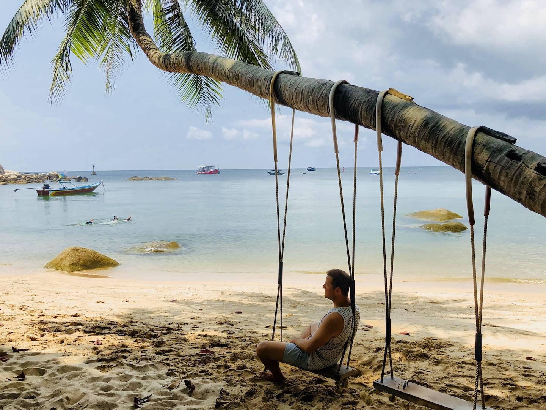 Mann auf Schaukel am Strand von Koh Tao