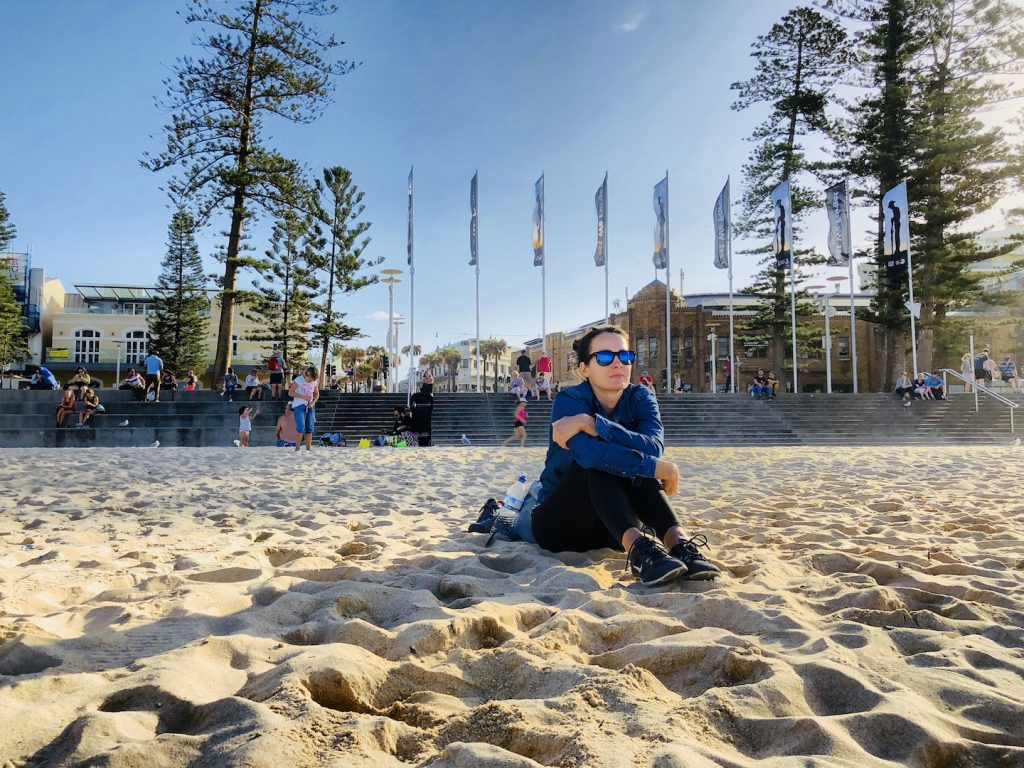 Frau sitzt am Manly Beach in Sydney
