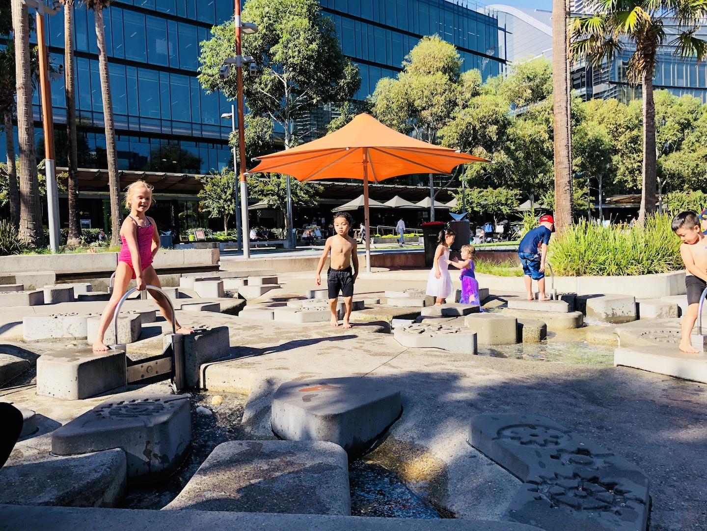 Kind auf Wasserspielplatz in Darling Quarter, Sydney
