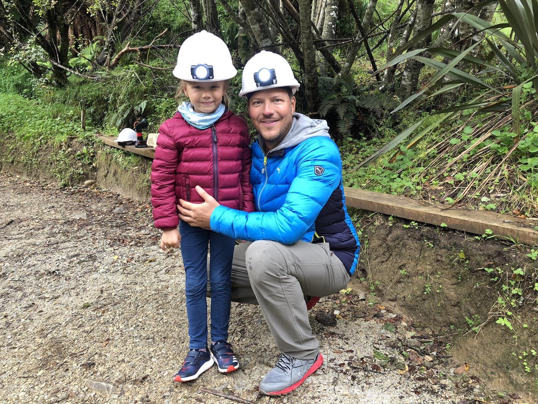 Vater mit Tochter mit Helm und Stirnlampe vor den Waitomo Caves, Neuseeland