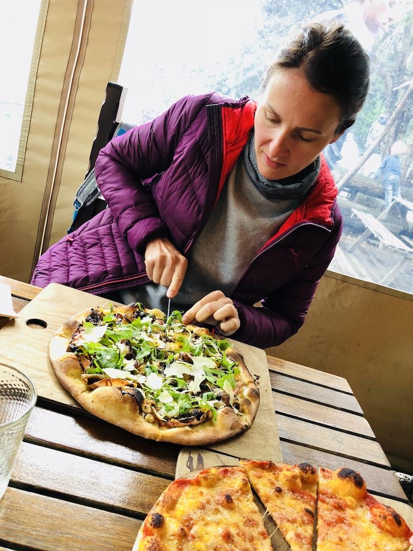 Frau isst Pizza bei Luke's Kitchen in Kuaotunu, Neuseeland