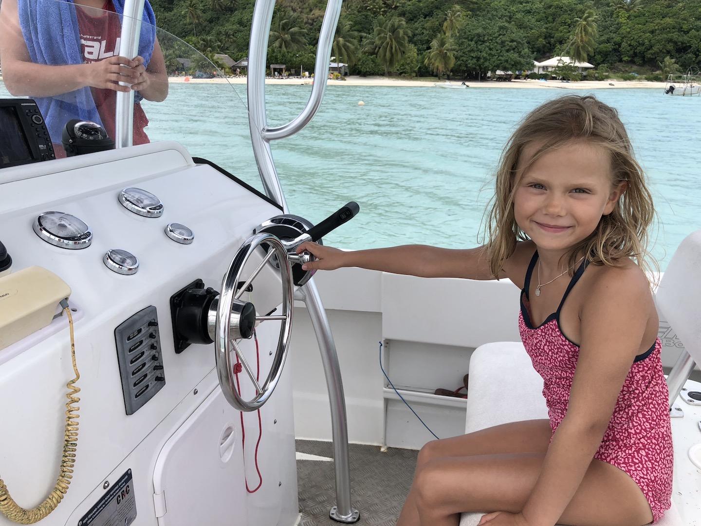 Kleines Mädchen am Steuer eines Motorbootes, Maupiti
