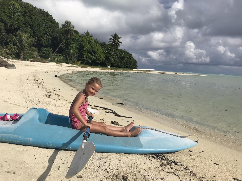 Mädchen im Kajak am Strand von Maupiti