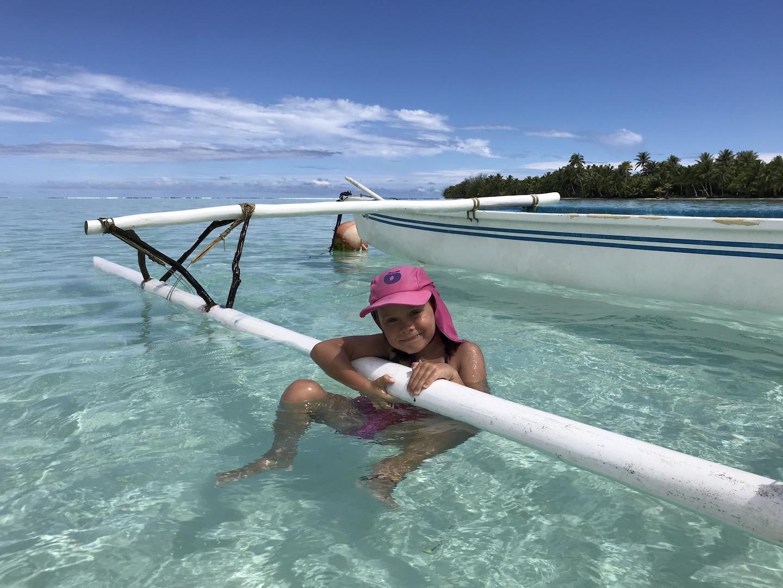 Mädchen im Wasser bei einem Kanu, Maupiti