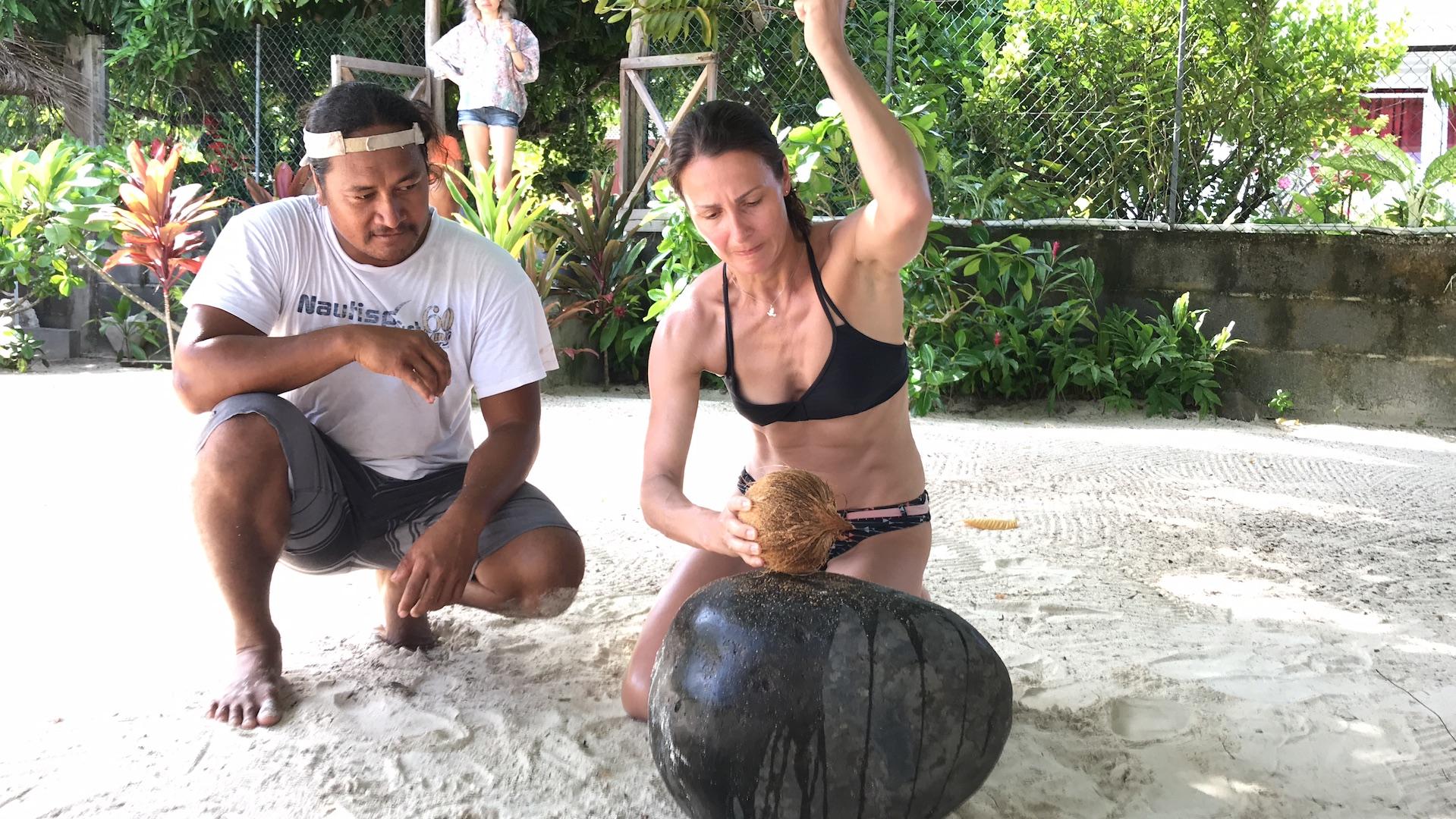 Frau versucht eine Kokosnuss aufzuschlagen mit der Hand, Maupiti