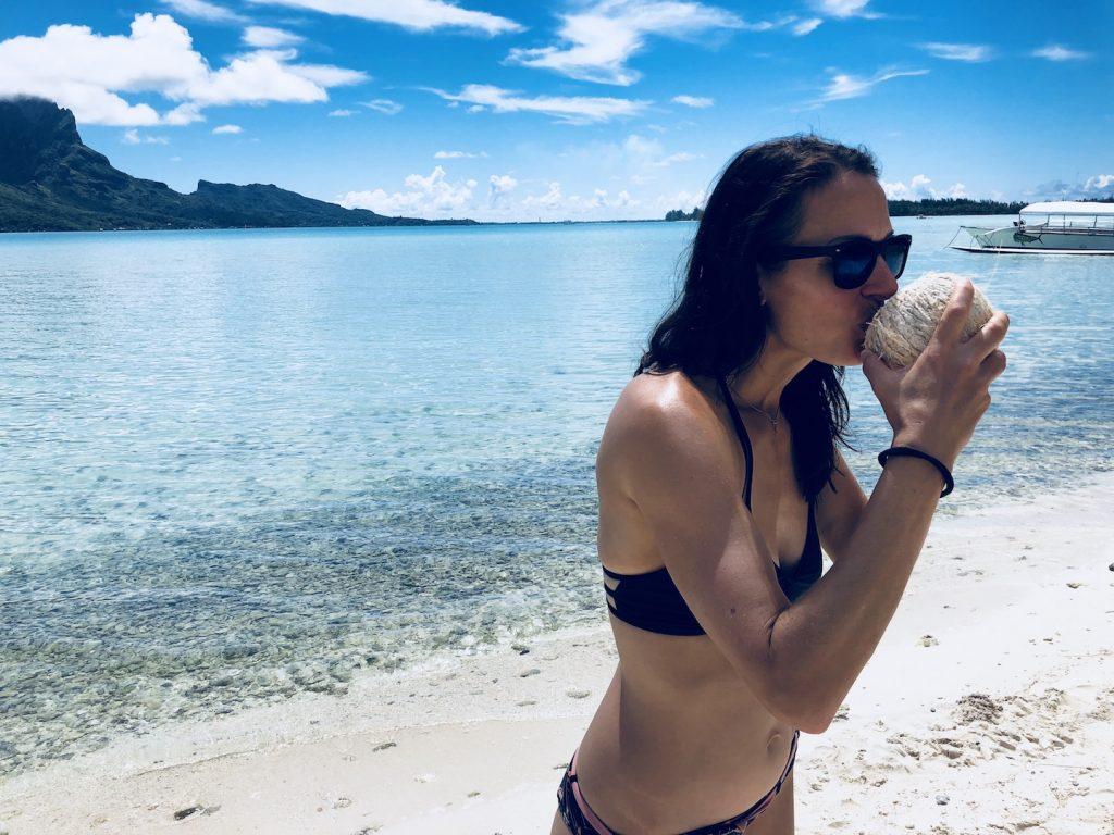 Frau trinkt Kokoswasser aus Kokosnuss auf Bora Bora