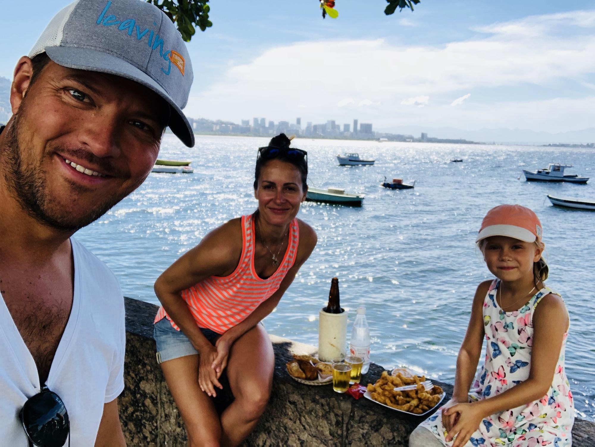 Familie isst bei der Bar Urca in Rio auf einer Mauer am Meer
