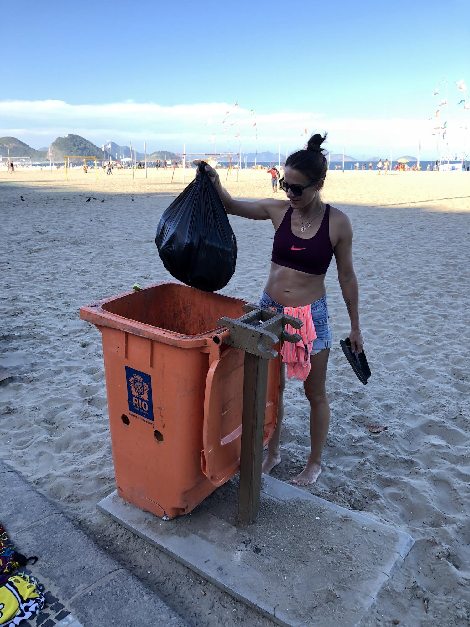 Frau schmeißt gesammelten Müll in die Mülltonne an der Copacabana in Rio