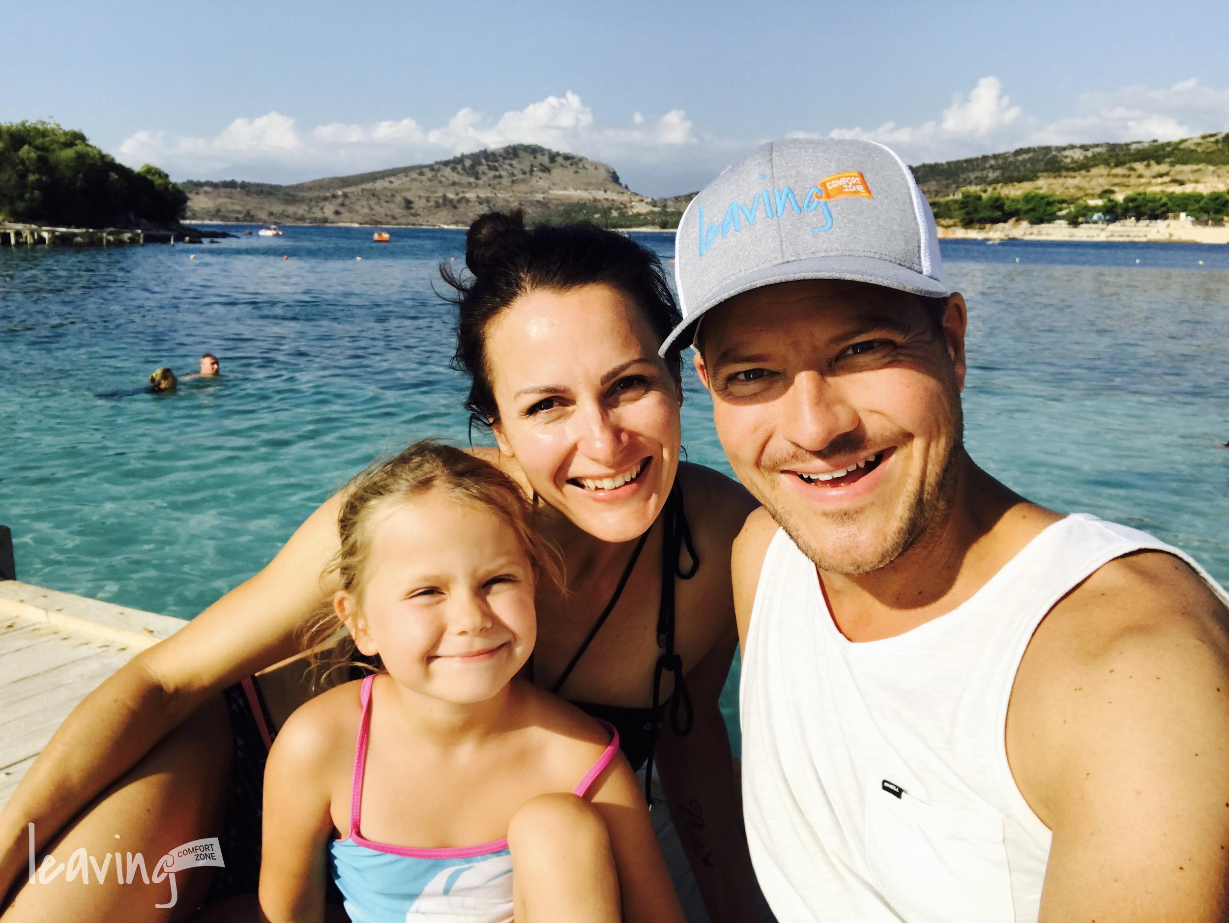 Vater, Mutter, Kind am Strand lächeln in die Kamera