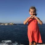 Kleines blondes Mädchen am Meer lächelt in die Kamera