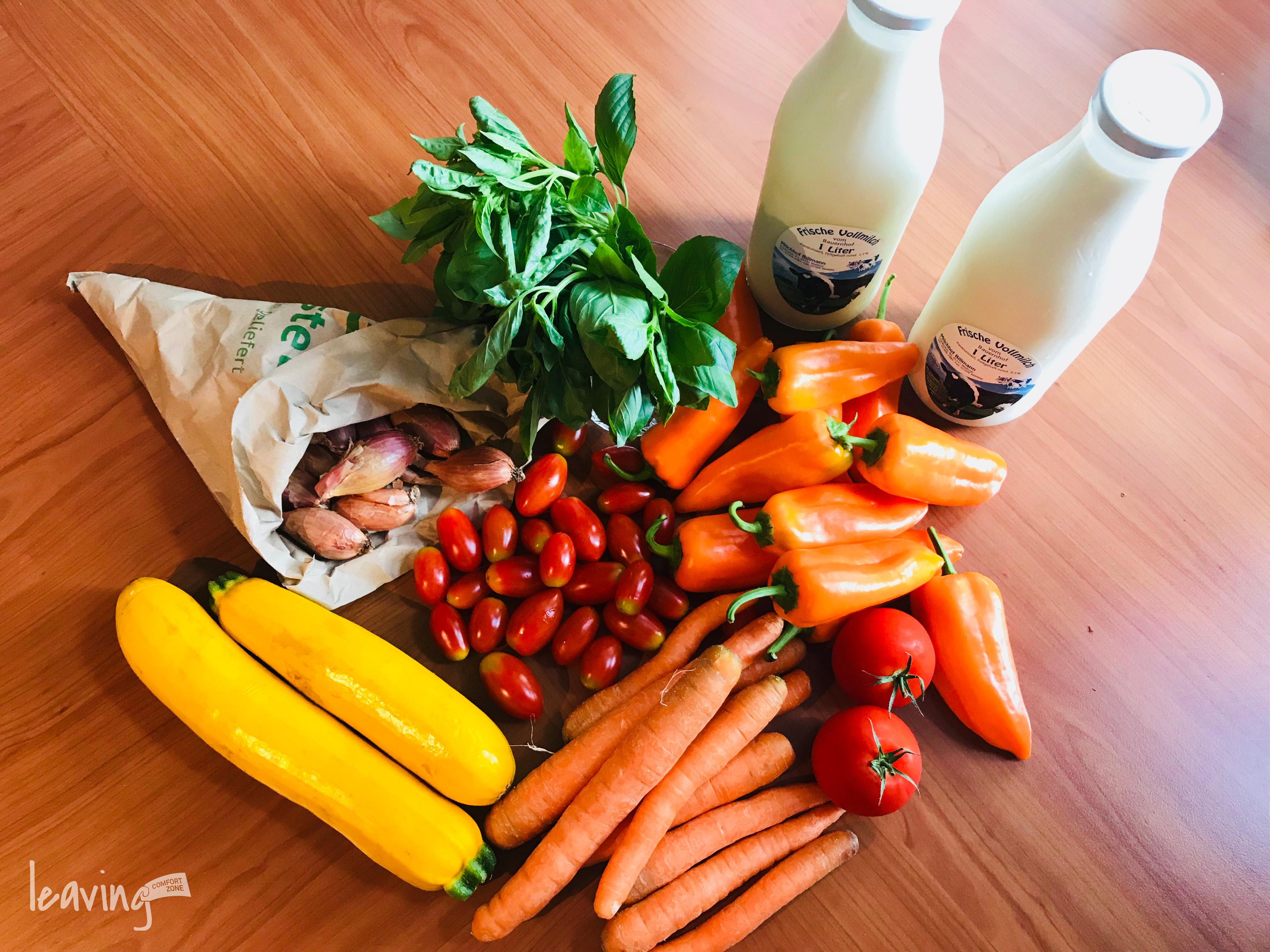 Frisches Obst und Gemüse und Milch in Glasflaschen
