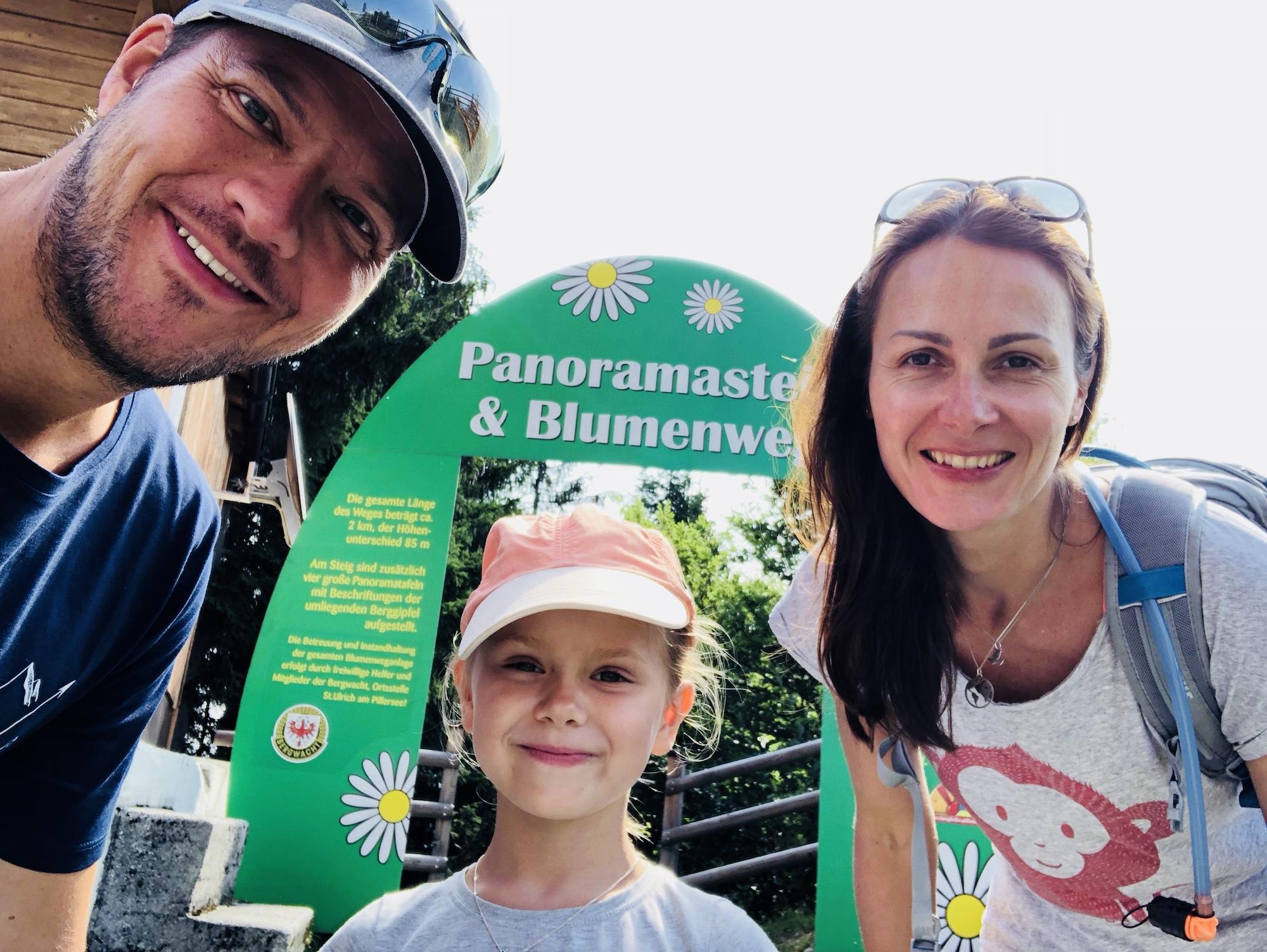 Familie vor dem Eingang zum Panoramasteig Blumenweg beim Jakobskreuz, Tirol in Österreich