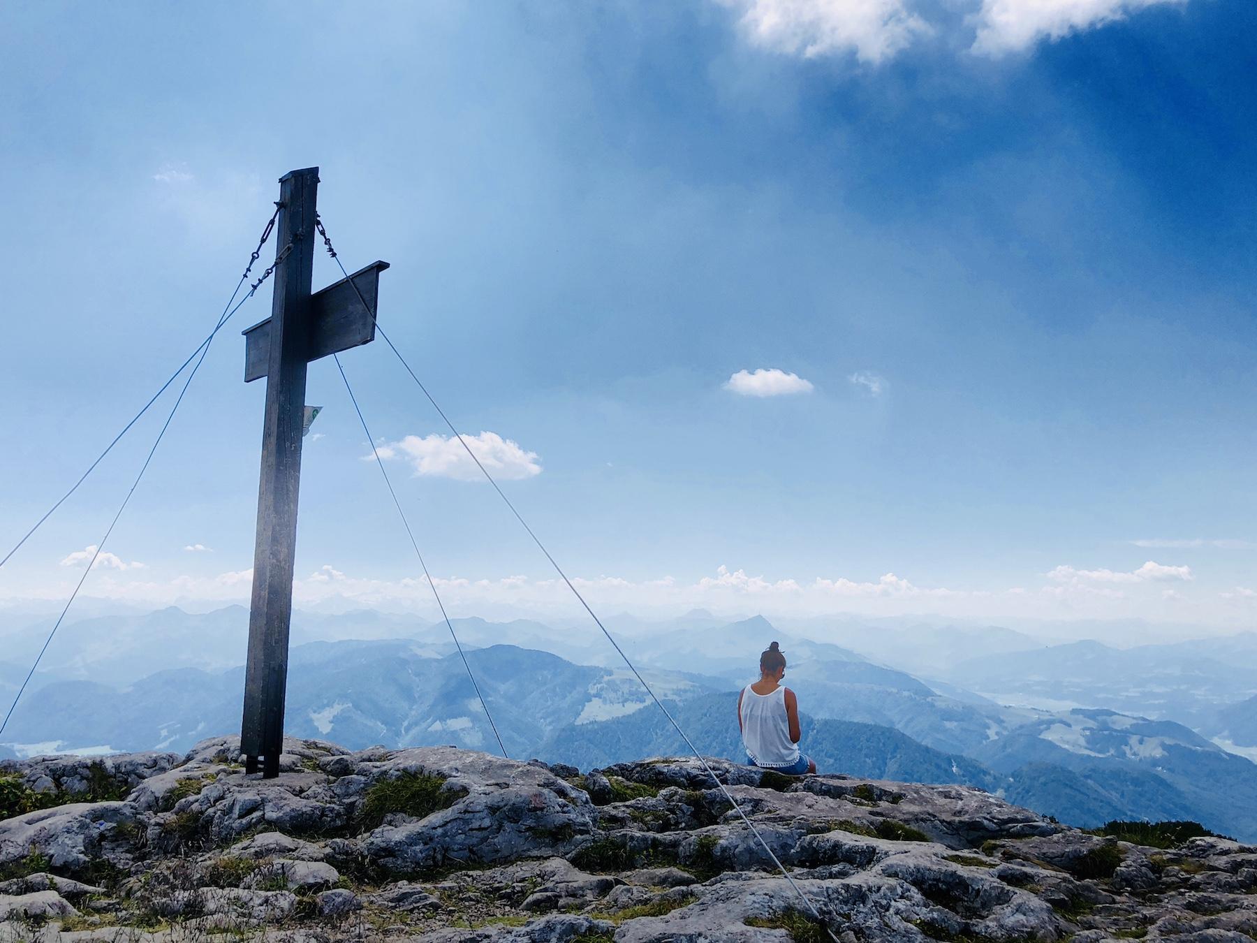 Frau sitzt neben einem Gipfelkreuz, Tirol, Österreich