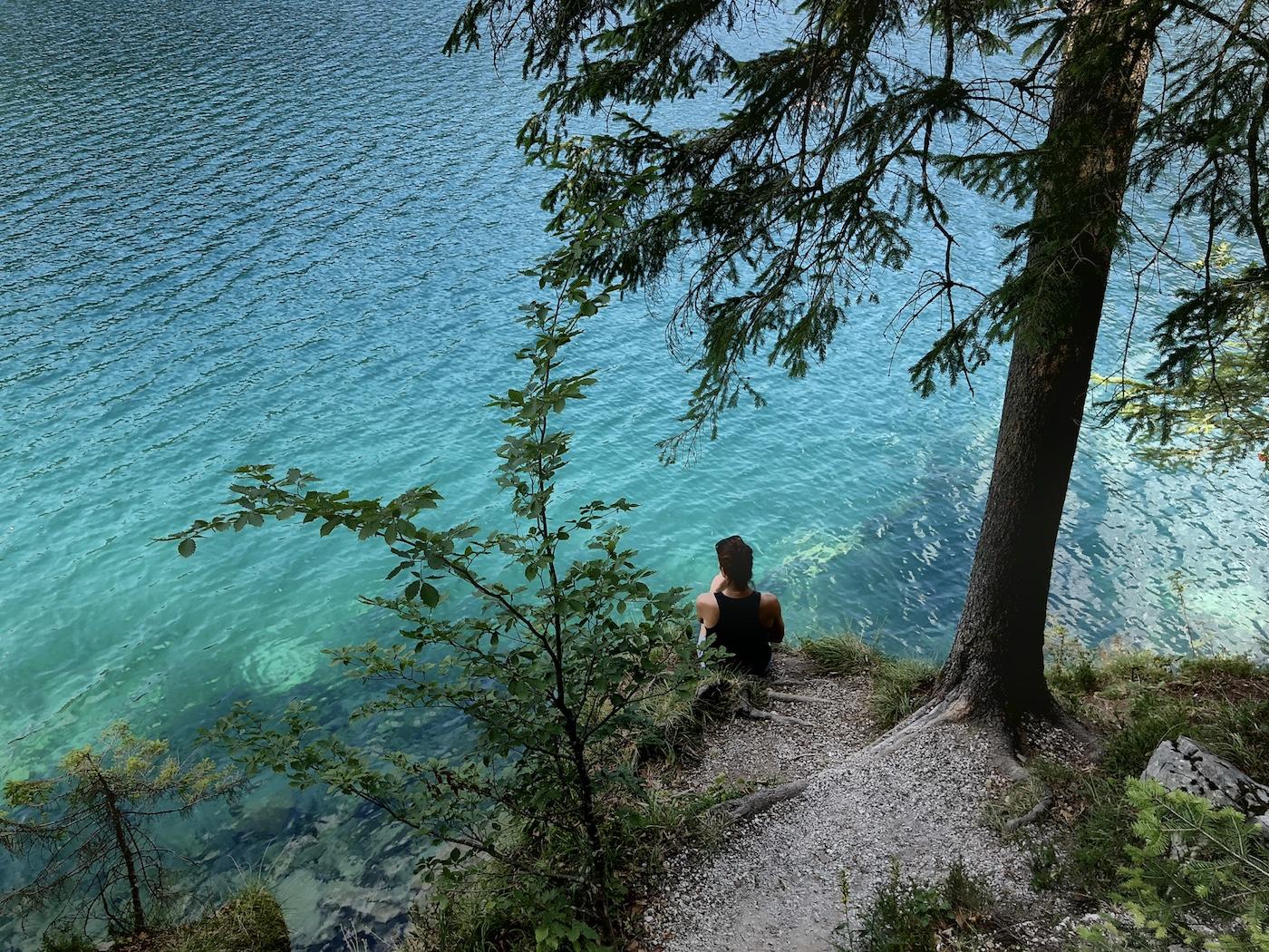 Frau am Ufer sitzend blickt auf Türkisfarbenes Wasser im Hintersteiner See, Tirol, Österreich