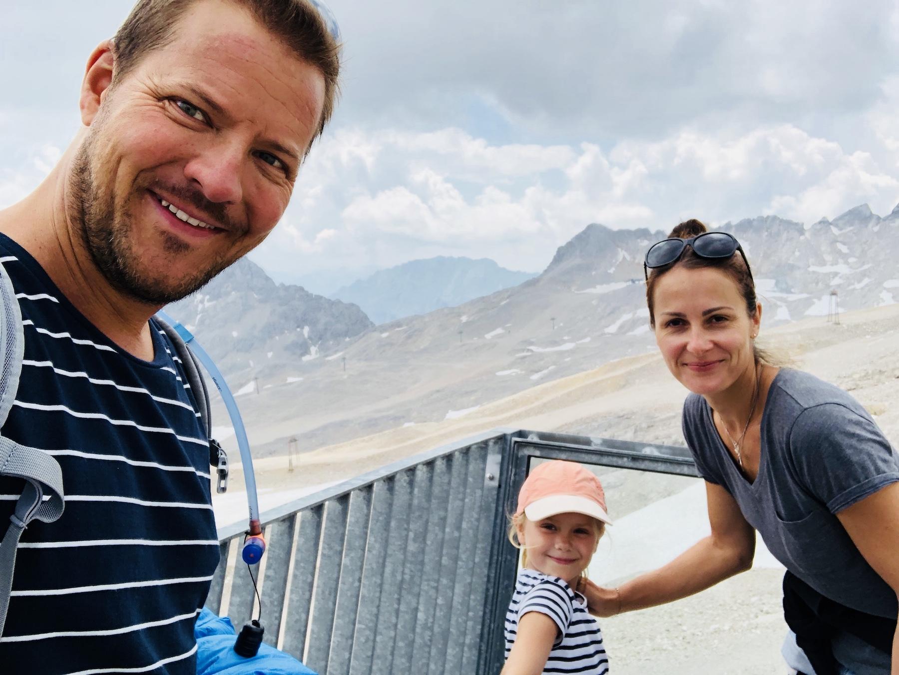 Familie auf der Zugspitze in die Kamera blickend