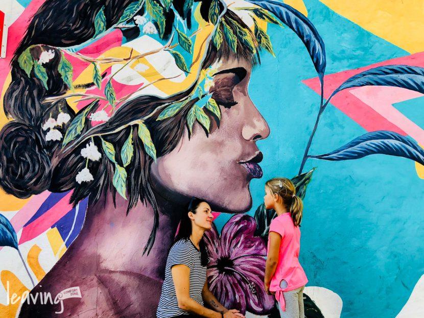 Mutter mit Kind vor einer Streetart in Südamerika