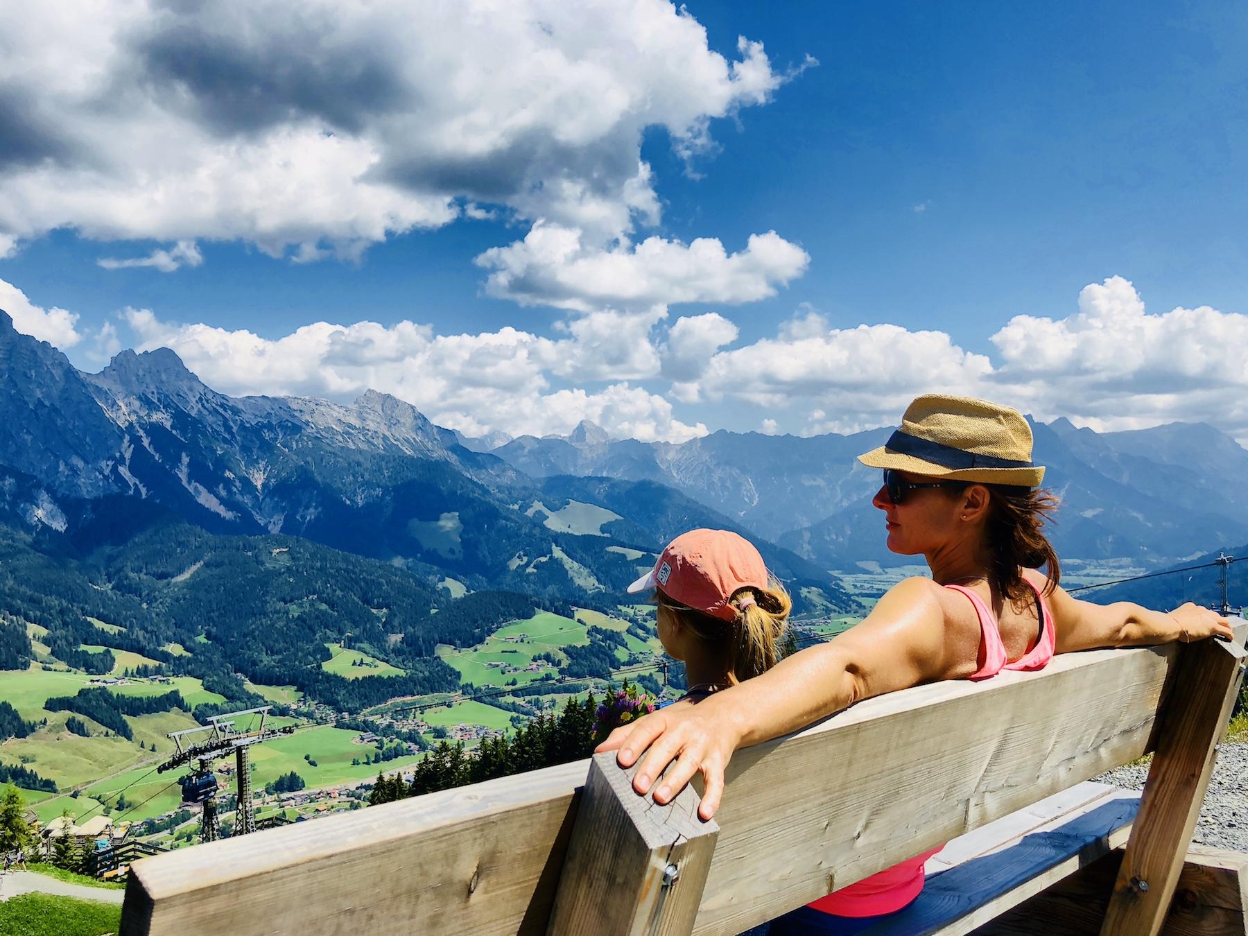 Mutter mit Tochter auf Bank in Tirol mit Blick auf die Berge