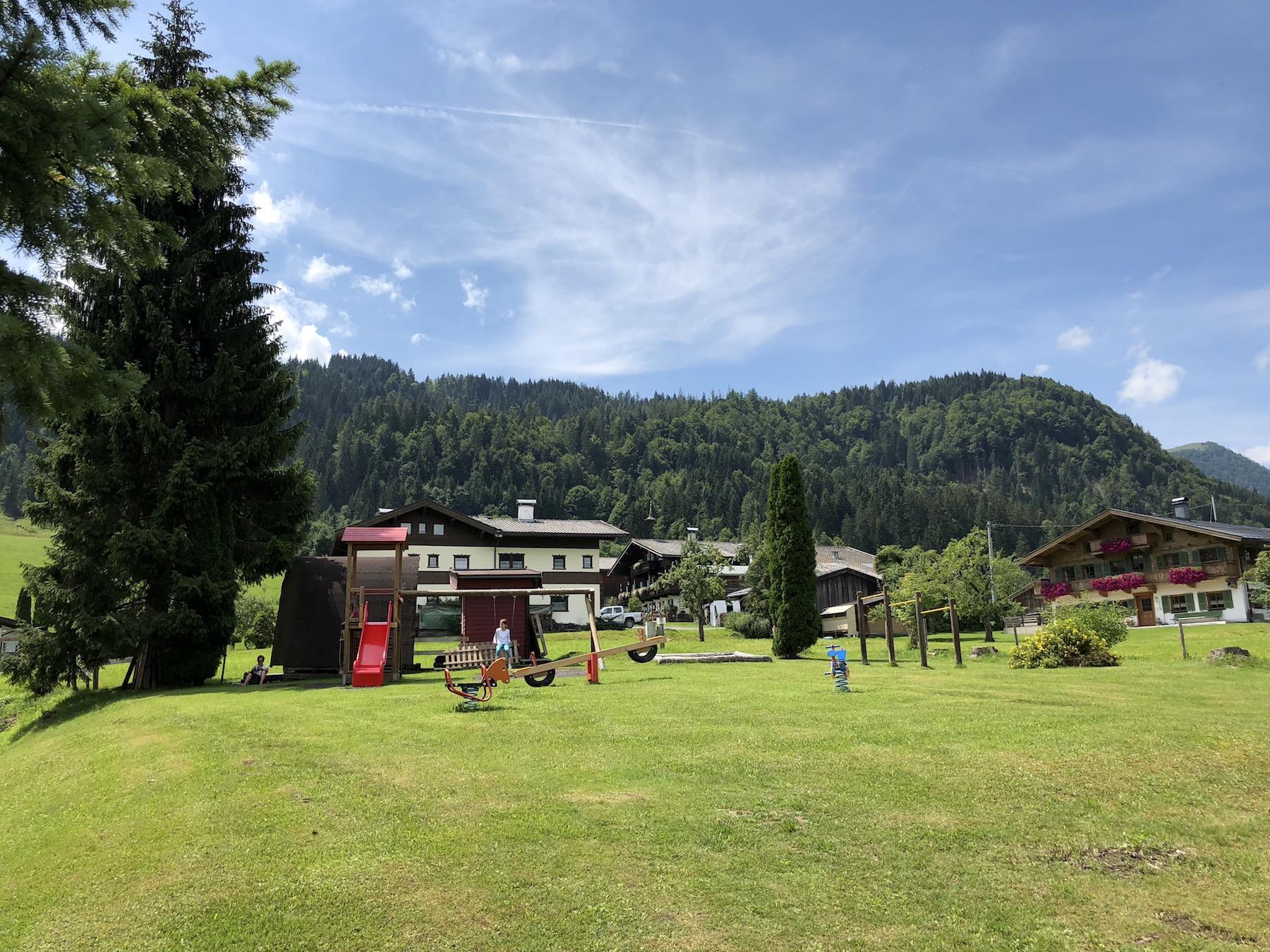 Grüne Wiese mit Spielplatz vom Hotel Fontana in Tirol, Österreich