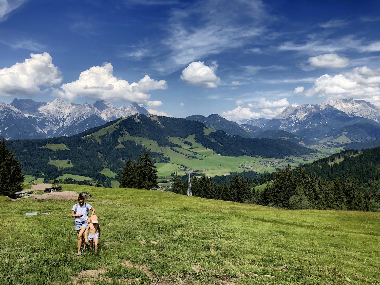 Frau und Kind wandern auf grüner Wiese, im Hintergrund die Berge, Tirol