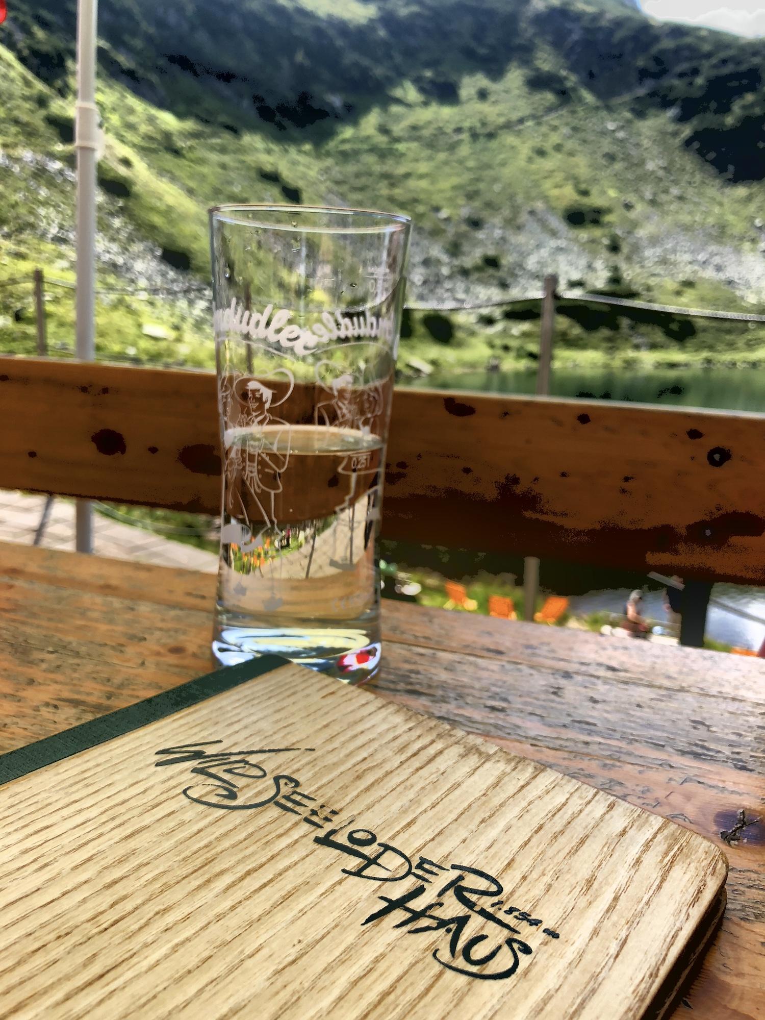 Glas mit Getränk auf einem Holztisch, im Hintergrund der Wildseeloderhaussee