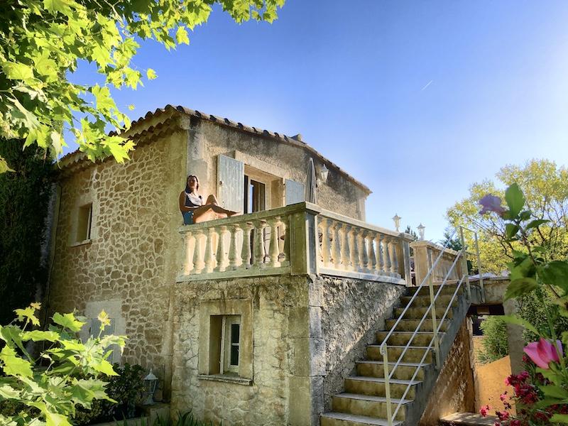 Frau auf einer Veranda eines Steinhauses in der Provence