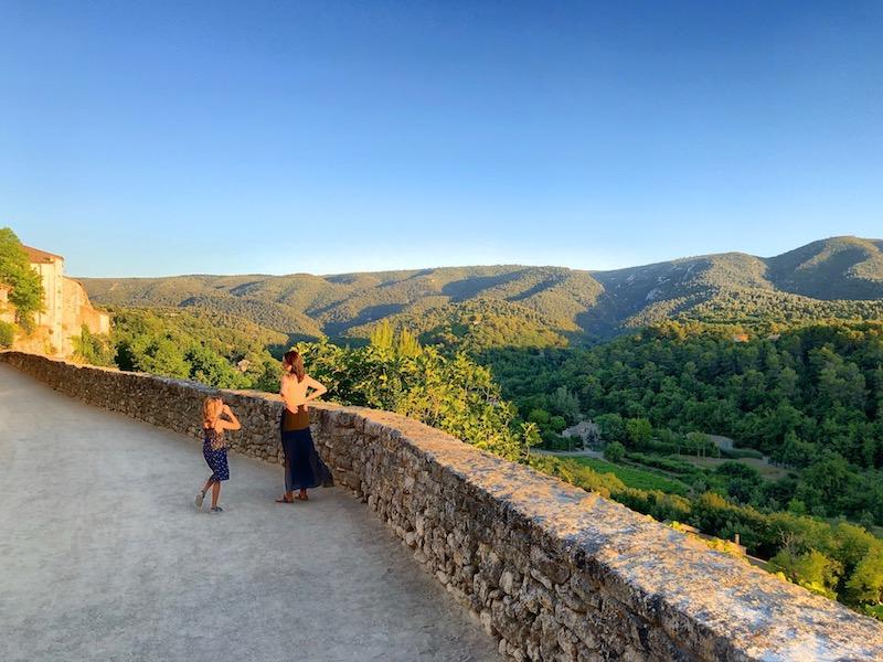 Frau mit Kind bei Stadtmauer von Ménerbes stehend, Ausblick auf die Täler von der Provence