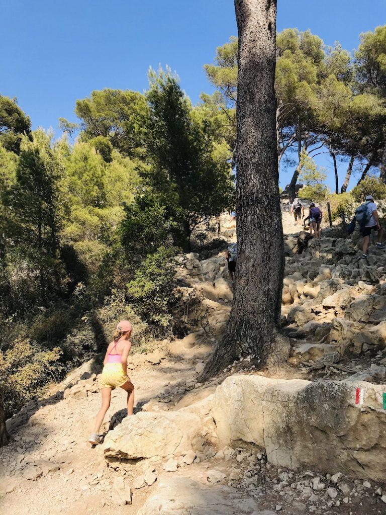 Mädchen läuft steilen Felsweg hoch bei den Calanques bei Cassis