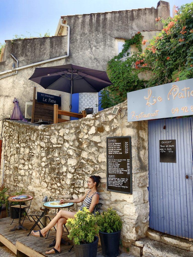 Frau an einem Tisch sitzend in einem Altstadtgässchen in Cassis